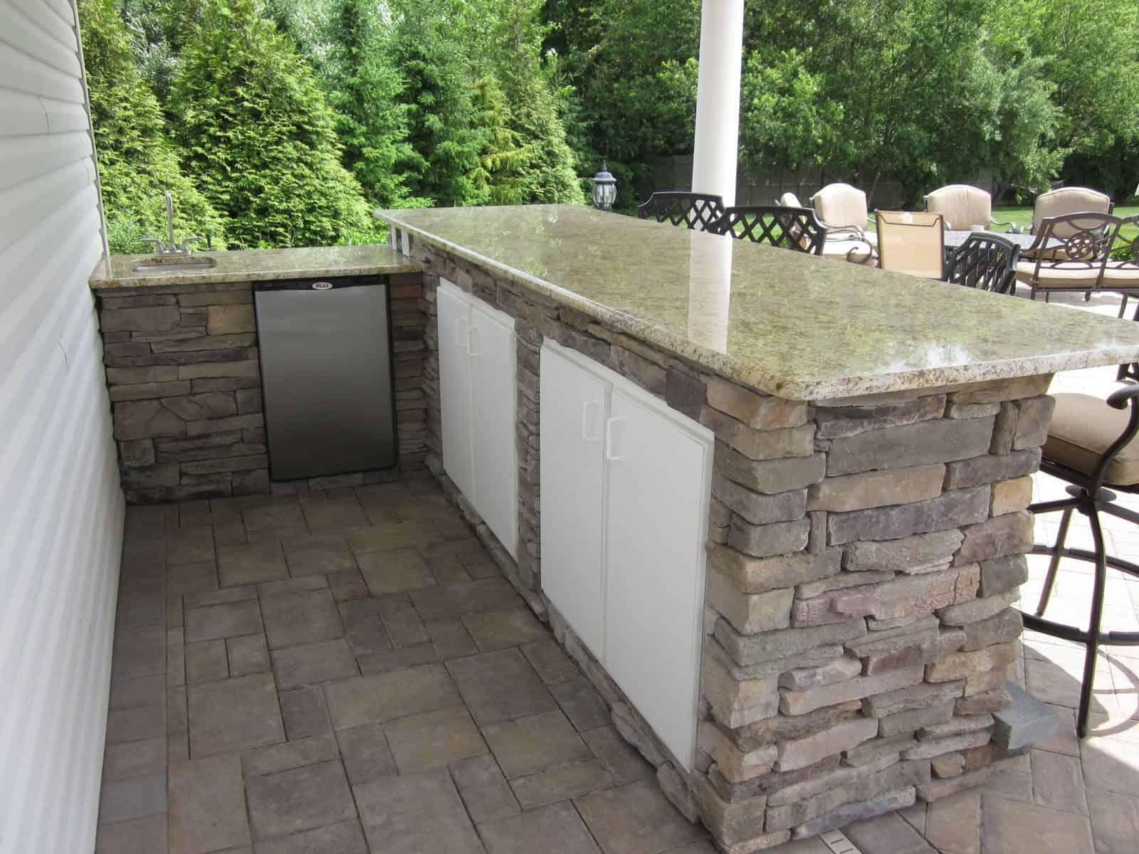 8' Custom Bar veneered with Cultured Stone Ledgestone veneer, Granite counter top, Bull stainless steel sink, custom cabinetry, fridge, and Rockfaced Bluestone foot rest - Dix Hills, Long Island NY