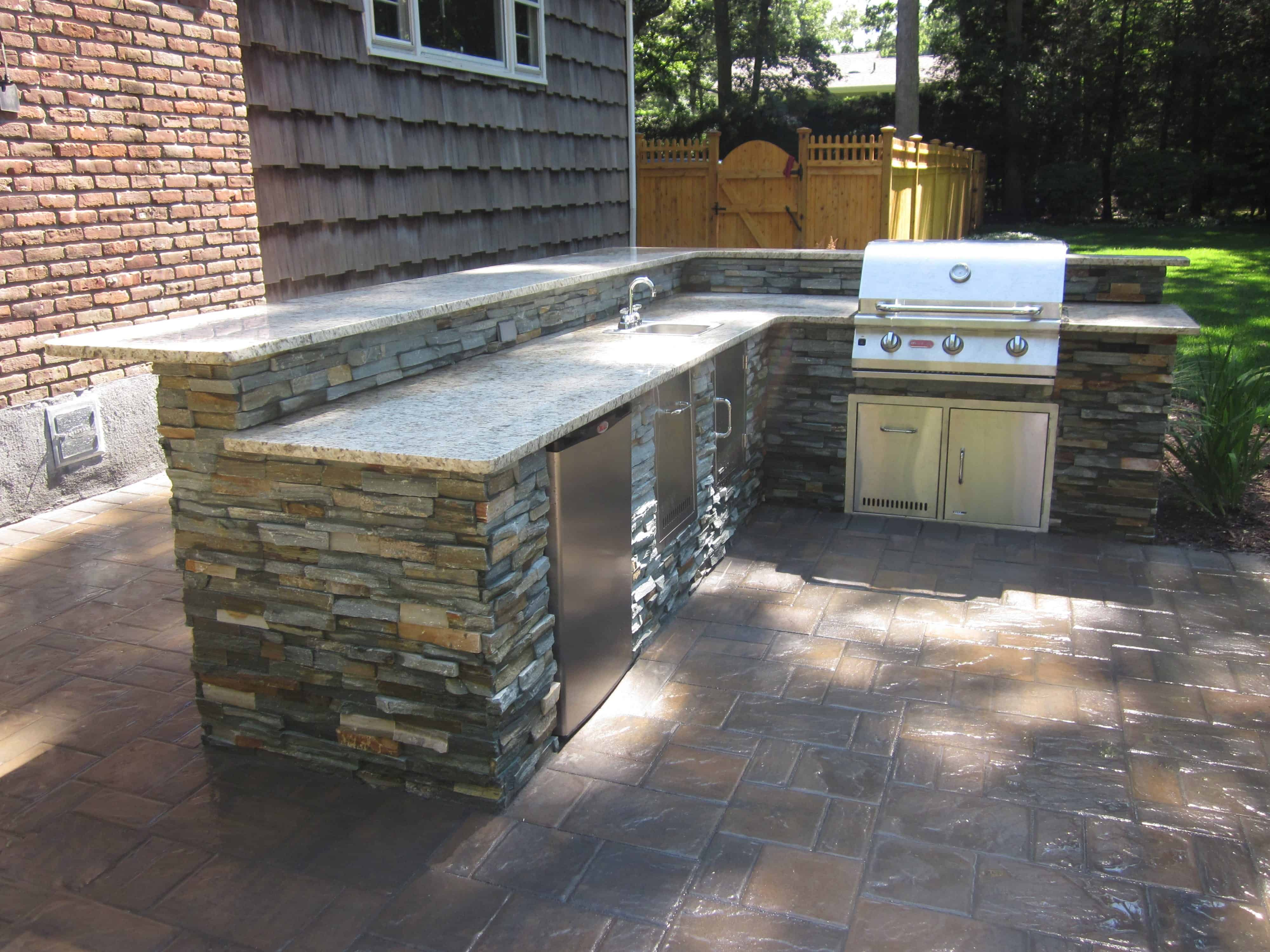 Outdoor Kitchen with Raised Bar veneered with East West Stone - Bayside Waters - Equipped with Brahma Grill, Access Doors, Sink w/ Access Door, Trash Drawer, and Refrigerator-Electrical outlets in backsplash - Dix Hills, Long Island NY