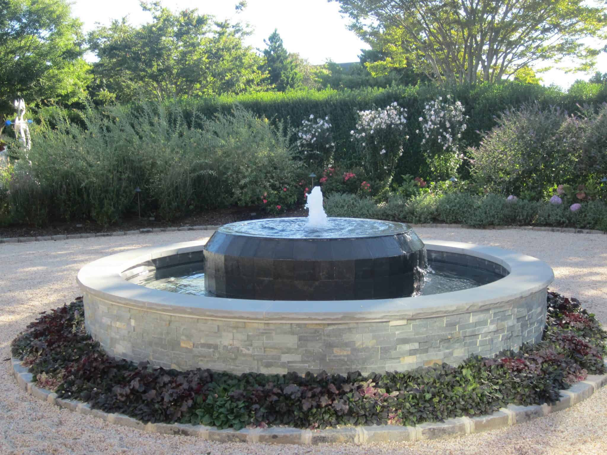 Gunite fountain with East West Stone veneer, Black Slate tile spill over, and rock faced Bluestone caps - Southampton, Long Island NY