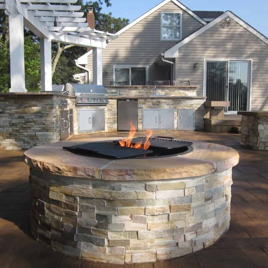 Outdoor Kitchen and Fire Pit Veneered with East West Stone - Honey Gold - and capped with Rainbow Stone with rock faced edge - Flanders, Long Island NY