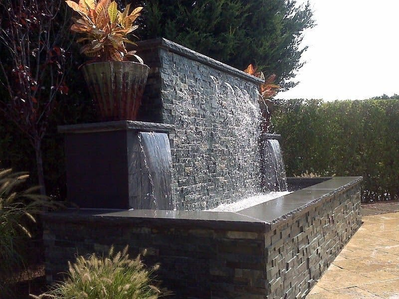 Gunite fountain veneered with East West Stone Waterwall, Black Slate tile Sheer Descents, and rock faced bluestone caps - Southampton, Long Island NY
