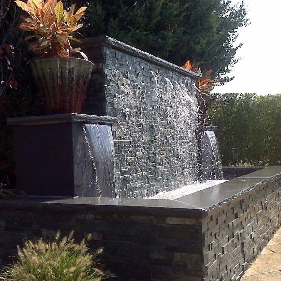 Gunite Fountain veneered with East West Stone Waterwall, Black State tile Sheert Descents, and rock faced bluestone caps