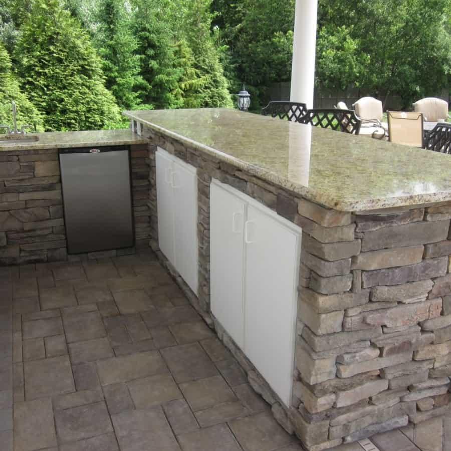 8' Custom Bar veneered with Cultured Stone Ledgestone veneer, Granite countertop, Bull stainless steel sink, custom cabinetry, fridge, and Rockfaced Bluestone footrest - Dix Hills, Long Island NY