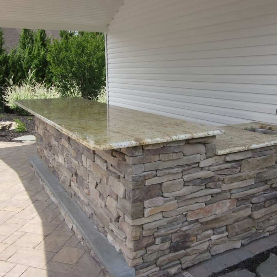 8' Custom Bar with Cultured Stone Ledgestone veneer, Granite countertop, Rockfaced Bluestone footrest, with Bull Stainless Steel sink and refrigerator