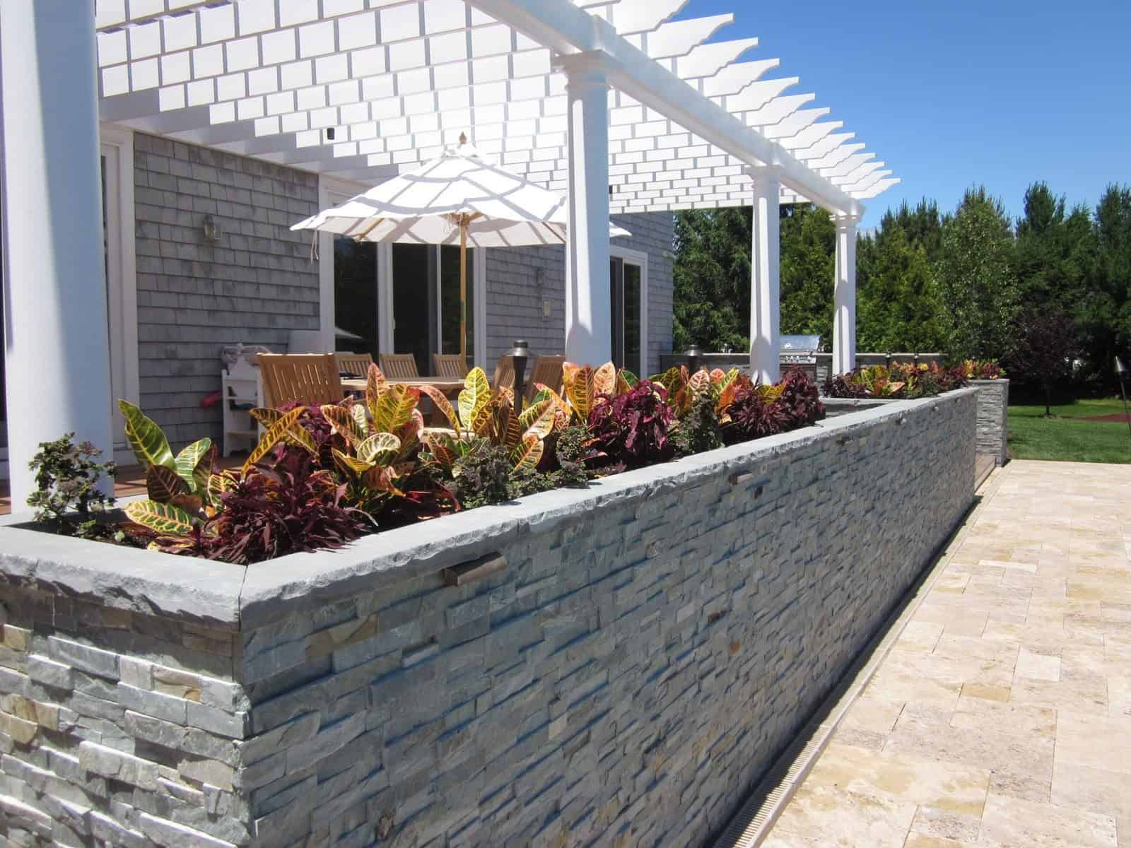 Custom Planters veneered with East West Stone - Bayside Waters - with Rockfaced Bluestone Cap planted with Coleus and Croton - Southampton, Long Island NY