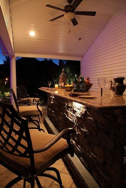 8' Custom Bar veneered with Cultured Stone Ledgestone veneer, Granite counter top, Bull stainless steel sink, custom cabinetry, and Rockfaced Bluestone foot rest - Dix Hills, Long Island NY