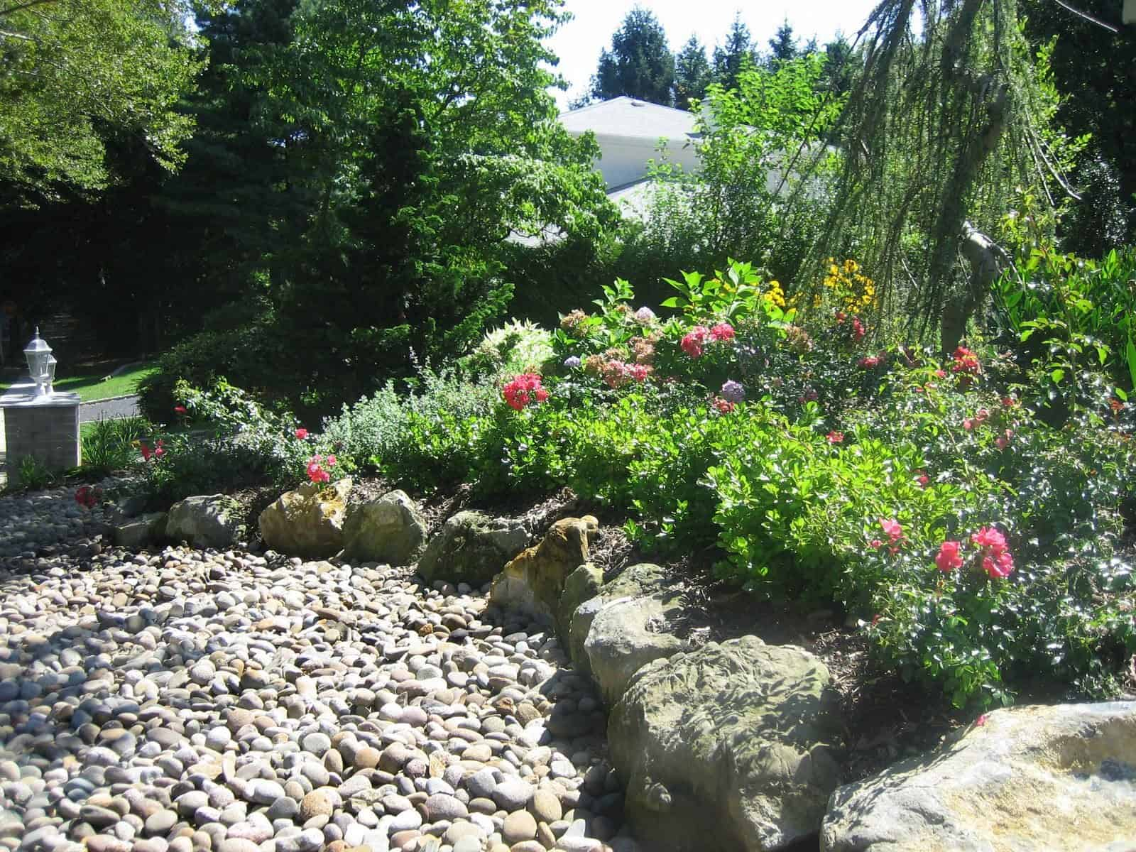 Moss rock retaining wall using 2' x 2' boulders - Dix Hills, Long Island NY