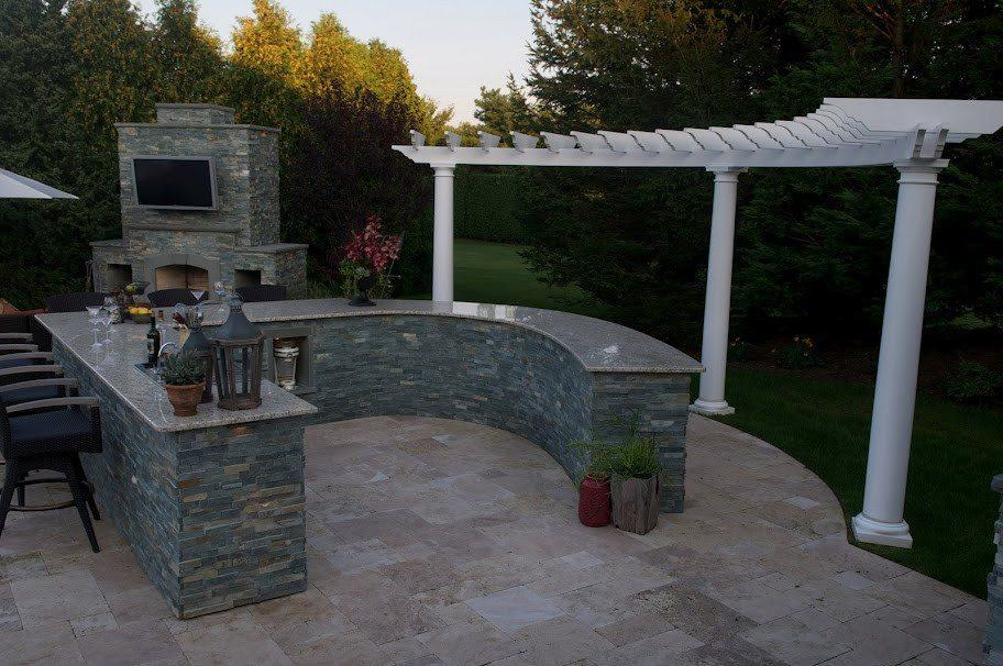 Radial Bar veneered in East West Stone - with granite countertop, Bull Stainless Steel sink, refrigerator, and custom shelving - Southampton, Long Island NY